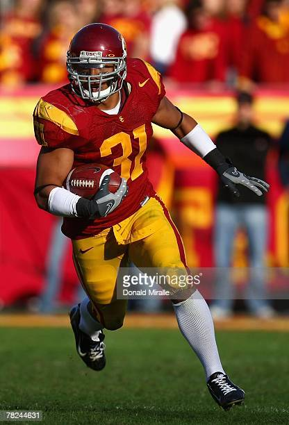 Runningback Stanley Havili of the USC Trojans carries the ball against the UCLA Bruins during the college football game at the Los Angeles Memorial...