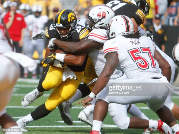 Runningback Toren Young of the Iowa Hawkeyes is wrapped up during the second half by linebacker Antonio Jones-Davis of the Northern Illinois Huskies...