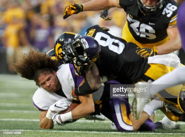 Runningback Xavior Williams of the Northern Iowa Panthers loses his helmet as he is brought down on a return in the first half by defensive back Matt...