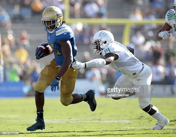 PASADENA CA SATURDAY OCTOBER 11 2014 UCLA runnng back Paul Perkins sprints past Oregon defender Ifo EkpreOlomu during second half action at the Rose...