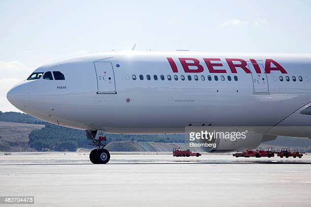 Runway tractors stand beyond an Airbus A330300 passenger jet operated by Iberia airlines a unit of International Consolidated Airlines Group SA on...