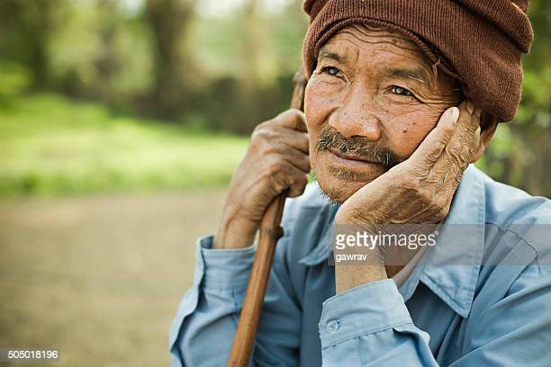 rural asian senior man thinking and looking away at sky. - nepalese ethnicity stock pictures, royalty-free photos & images