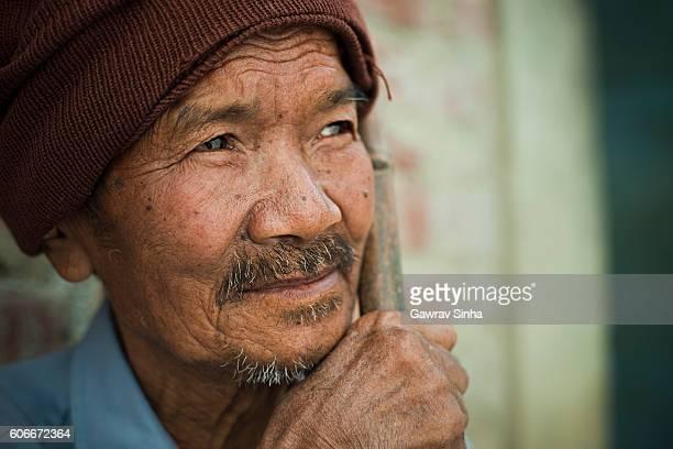 Rural Asian serene, senior peasant man thinking and looking away.