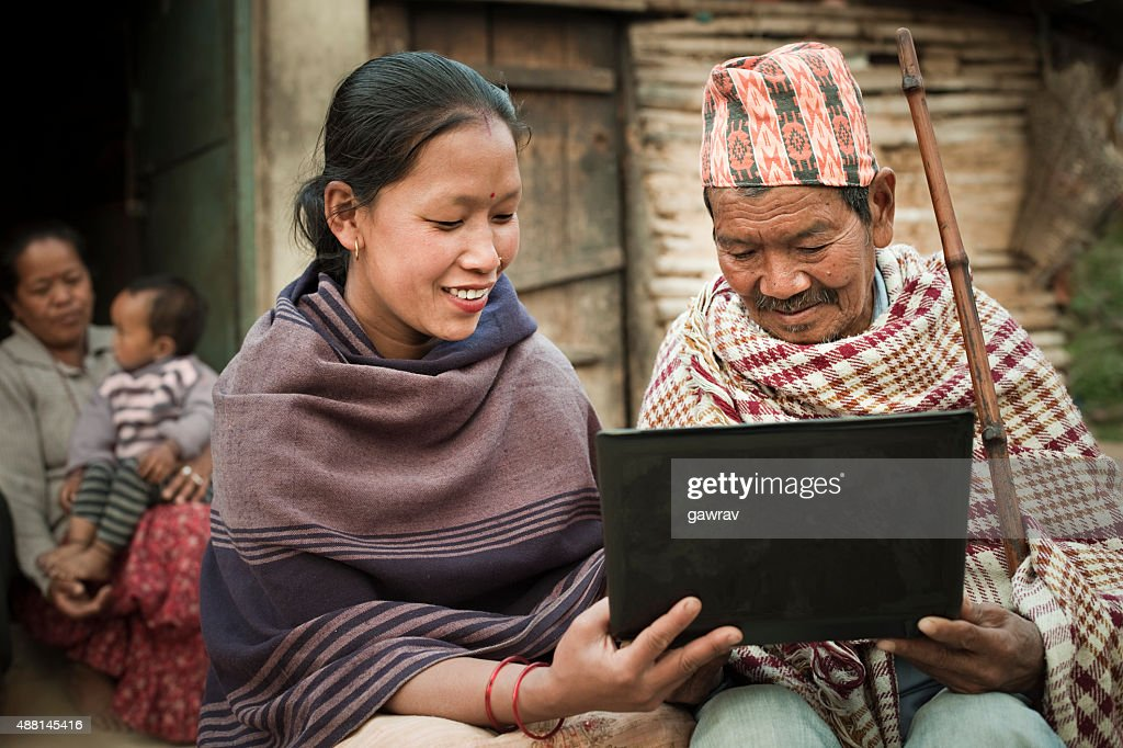 Rural Asian young woman showing laptop to a senior man. : Stock Photo