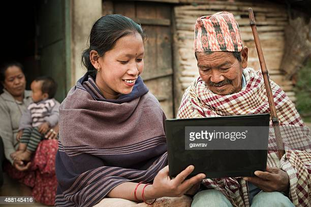 Rural Asian young woman showing laptop to a senior man.