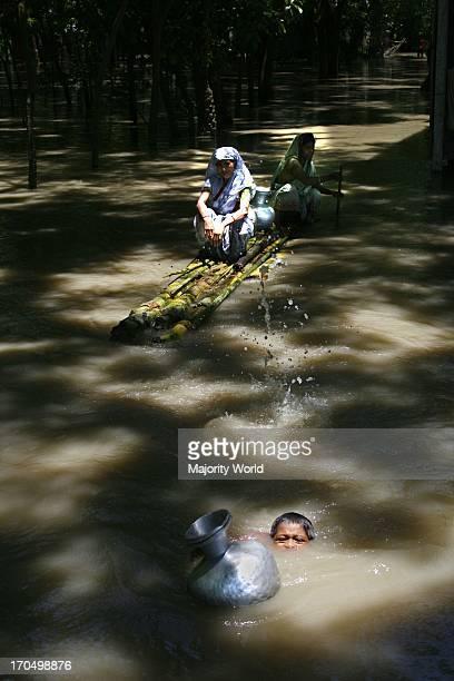 A rural boy swims ahead of banana raft to collect fresh water at flood affected Dohar Munshiganj Bangladesh August 5 2007