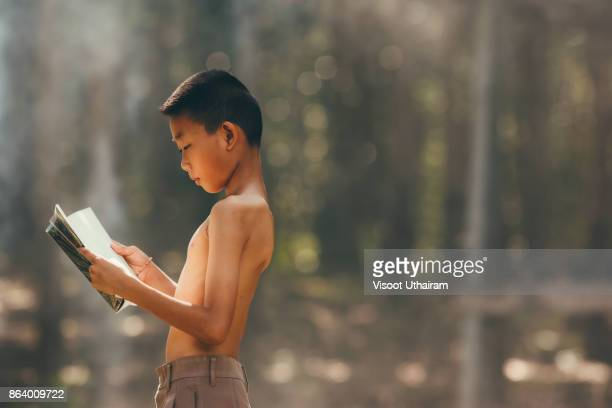 Rural children are reading a book at the forest.