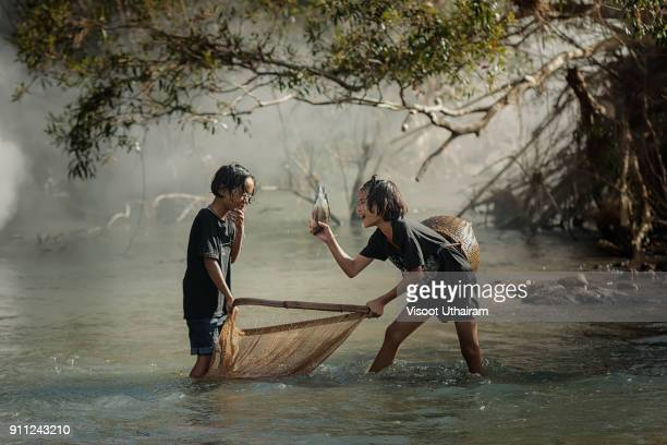 Rural children fishing at the river