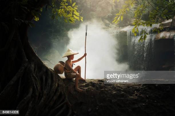 Rural children fishing in thr forest.