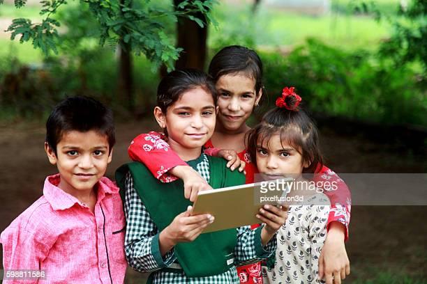 Rural children holding digital tablet