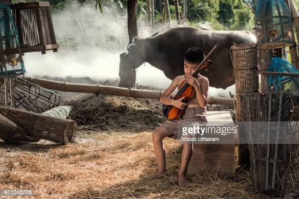 Rural children playing violin at countryside.