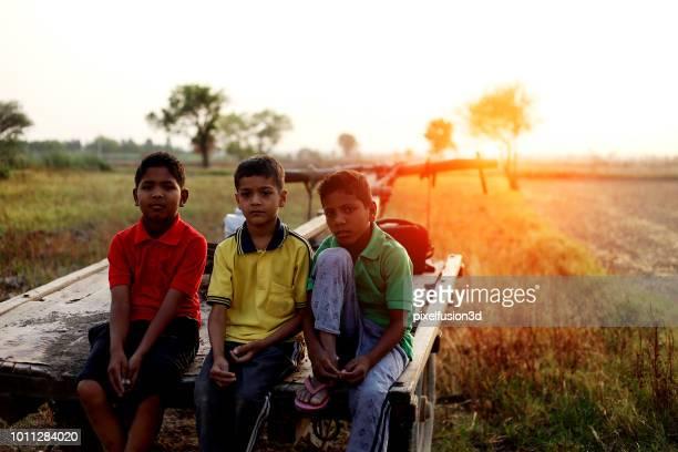 ländliche kinder porträt im freien sitzen - ox cart stock-fotos und bilder