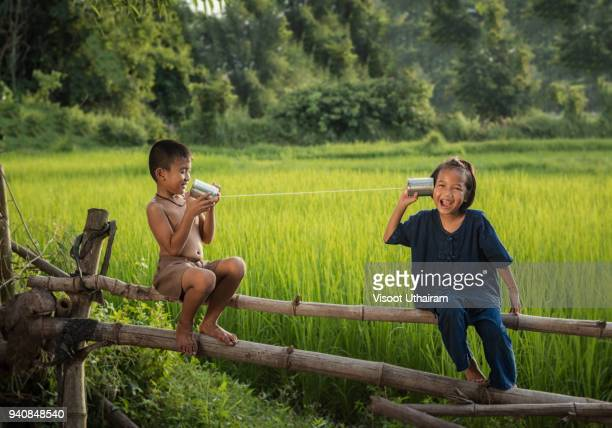 Rural children talking on a can phone.