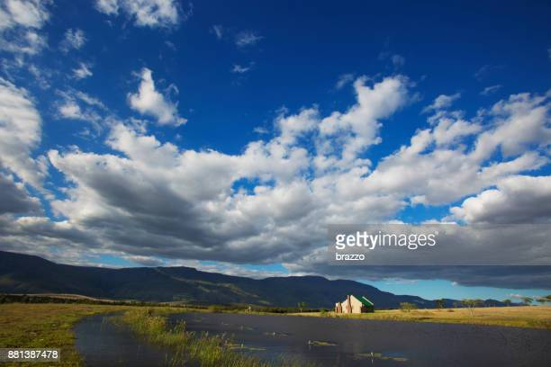 Rural cloudscape with cottage and mountains, brief code 700031830
