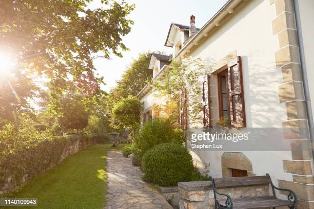 rural cottage and garden in sunlight - cottage exterior stock pictures, royalty-free photos & images