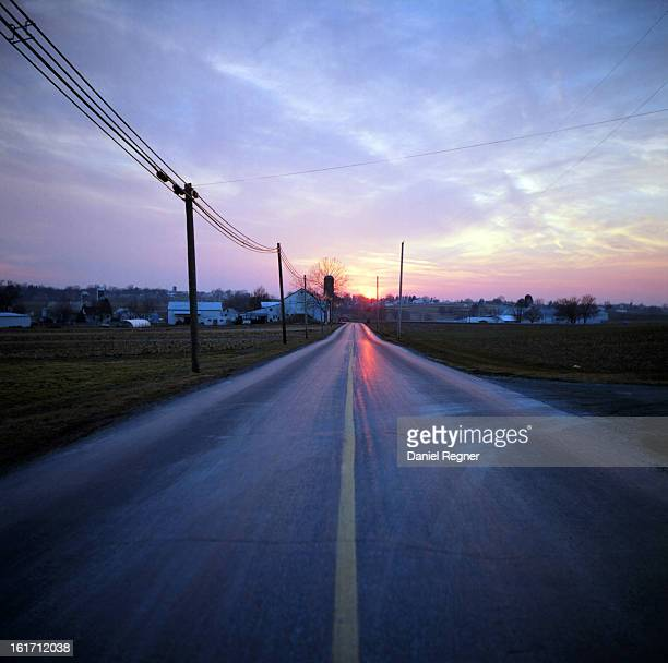 Rural country road during the sunset. The warm pink and red sky can be seen reflected in the shiny tar of the road. The sky is lit with a beautiful...