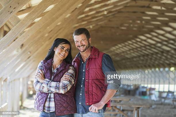 Rural couple standing inside farm building