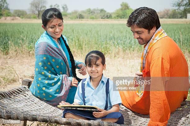 Rural couple teaching their daughter, Sohna, Haryana, India