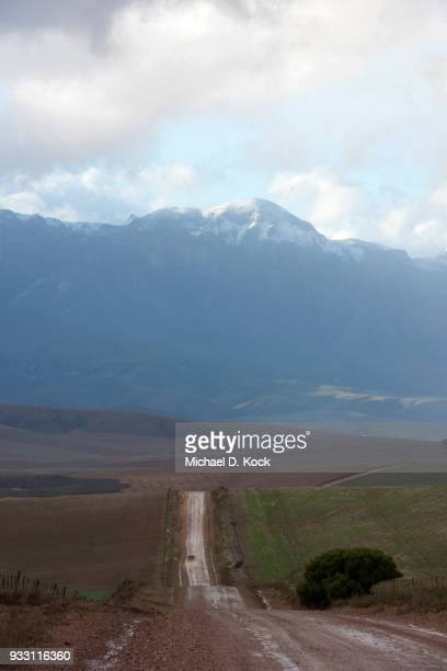 rural dirt road after a rainstorm, vehicle heading towards the snowcapped riviersonderend mountains, overberg, western cape - overberg stock pictures, royalty-free photos & images
