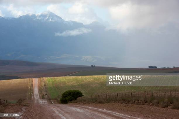 rural dirt road after a rainstorm with the snowcapped riviersonderend mountains in the background, overberg, western cape - overberg stock pictures, royalty-free photos & images