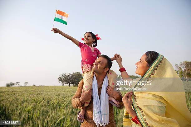 Rural family in the field with girl holding Indian flag