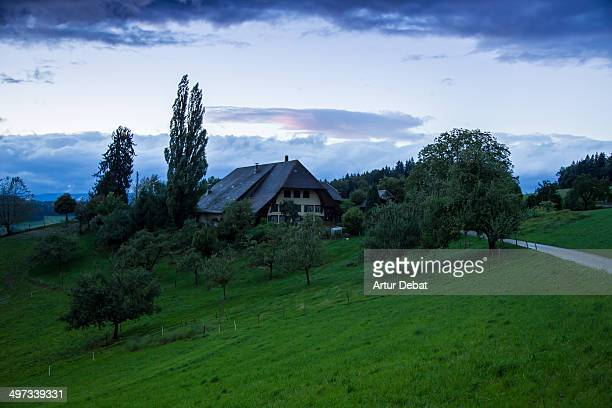 Rural farm with barn in the Swiss countryside on sunrise in a road trip through Switzerland