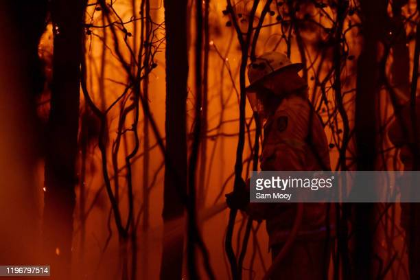 Rural Fire Service firefighter conducts mopping up near the town of Sussex Inlet on December 31 2019 in Sydney Australia There are a number of...