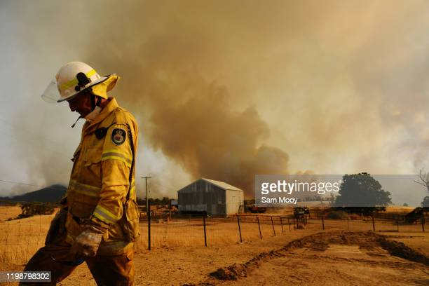 Rural Fire Service firefighter Trevor Stewart views a flank of a fire on January 11, 2020 in Tumburumba, Australia. Cooler temperatures forecast for...