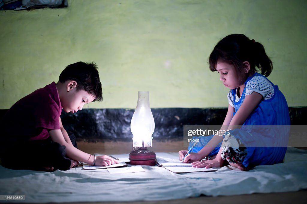 Rural girl and boy studying in lantern : Stock Photo