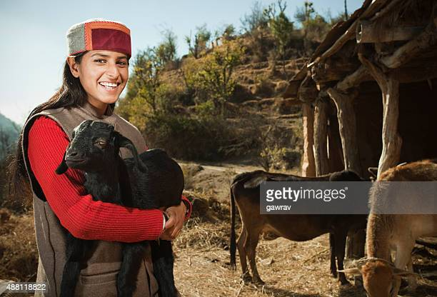 Rural girl carrying goat kid in arms at hilly area.