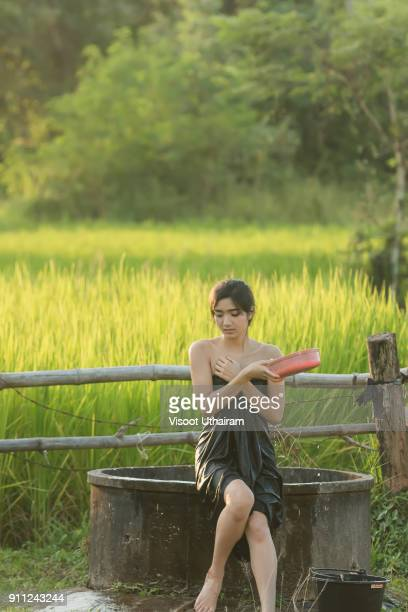 Rural girl is taking a shower from a traditional Groundwater.