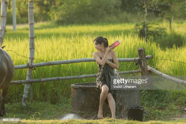 rural girl is taking a shower . - pretty vietnamese women stock photos and pictures