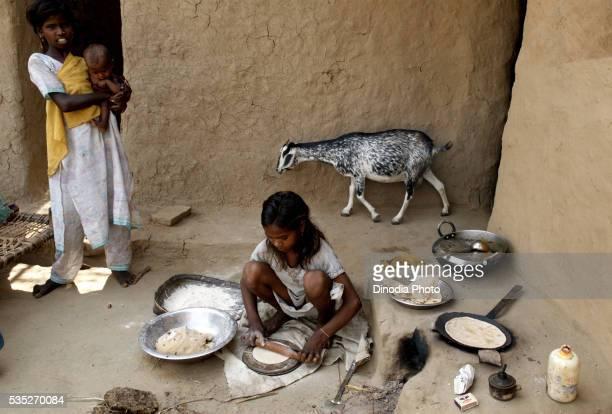 Rural girl preparing food in a kitchen in Rajouli, Nawada, Bihar, India.