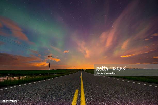 rural highway leads into prairie sunset - empty road stock pictures, royalty-free photos & images