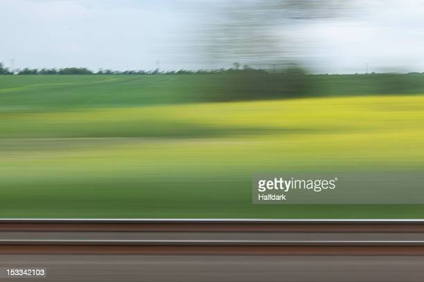 a rural landscape in blurred motion viewed from a moving train - bewegungsunschärfe stock-fotos und bilder