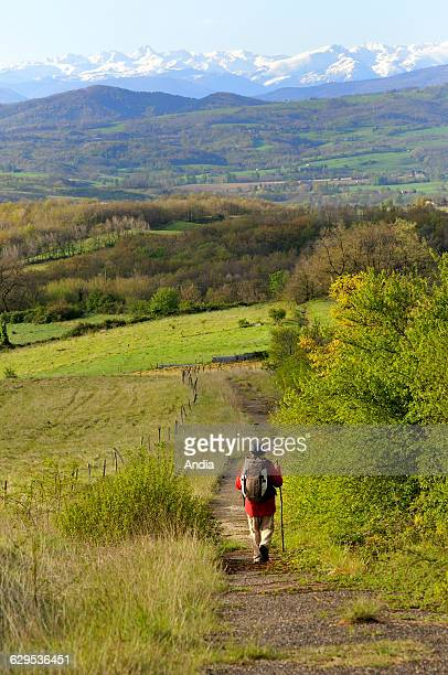 Rural landscape in the PrePyrenees between Pamiers and Le Mas d'Azil in the Ariege department Pilgrim carrying a backpack walking on a path