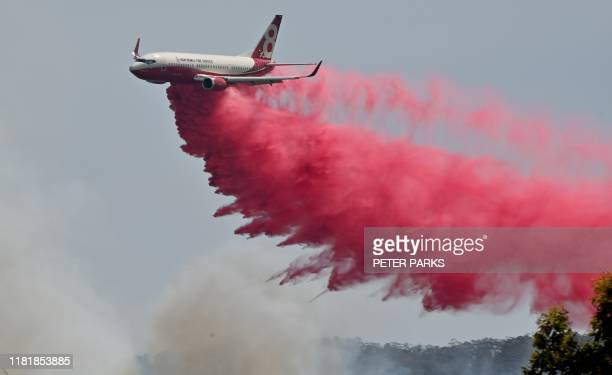 Rural NSW Fire Service plane drops fire retardent on an out of control bushfire near Taree 350km north of Sydney on November 12 2019 A state of...