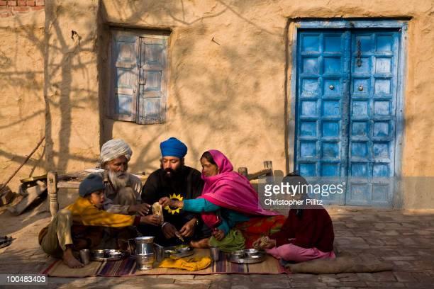 A rural Punjabi family sit down for breakfast