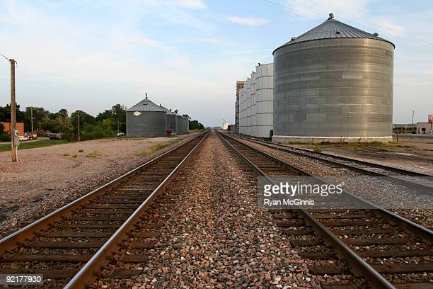 rural railroad tracks with grain silos - ryan mcginnis stock photos and pictures