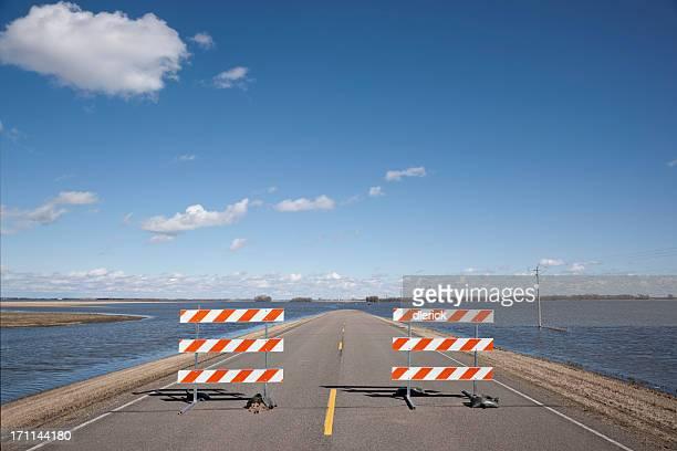 rural road blocked by flood waters