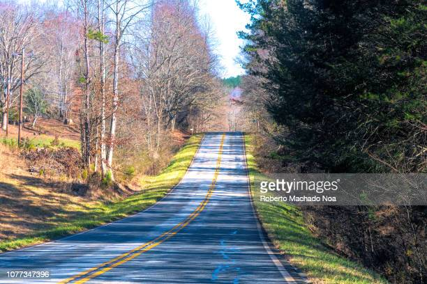 Rural road during the Winter season. Beauty in nature seen from a driving car during the daytime.