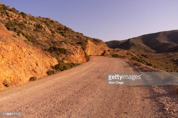 rural road in a semi-desert landscape. south spain. - land feature stock pictures, royalty-free photos & images