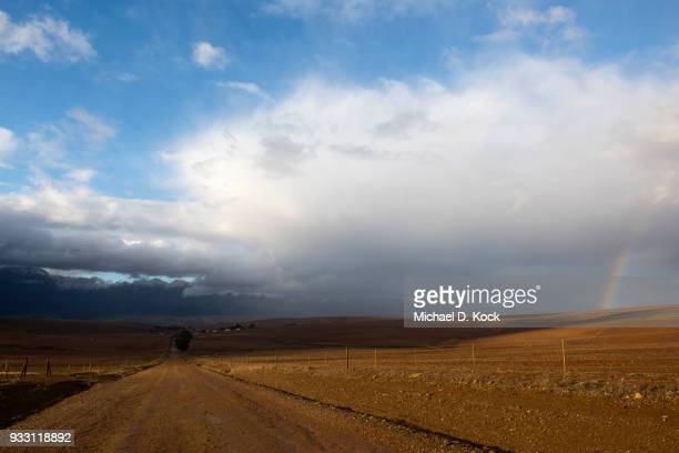 rural road leading towards a farm and the riviersonderend mountains, snow covered and storm clouds with a rainbow, overberg, western cape - overberg stock pictures, royalty-free photos & images
