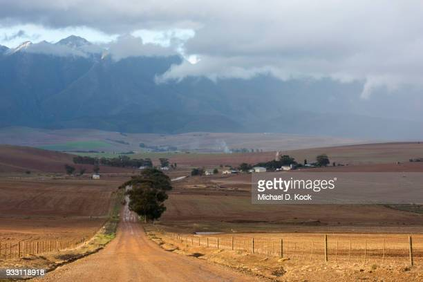 rural road leading towards a farm and the riviersonderend mountains, snow covered, storm clouds moving east, overberg, western cape - overberg stock pictures, royalty-free photos & images