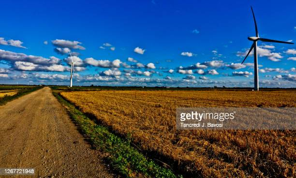 rural road on landscape of wind turbines - bavosi stock pictures, royalty-free photos & images