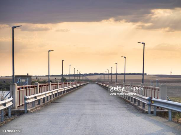 rural road over a bridge, with railing and guardrails at sunset - 散歩道 ストックフォトと画像