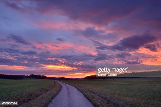 Rural road with dramatic sunrise.