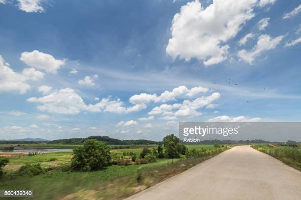 Rural road with rice paddies in side under blue sky with clouds