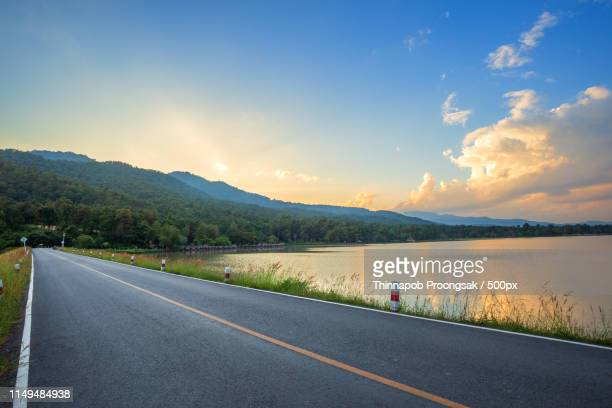 rural road with scenic view of the reservoir huay tueng tao with - flussufer stock-fotos und bilder