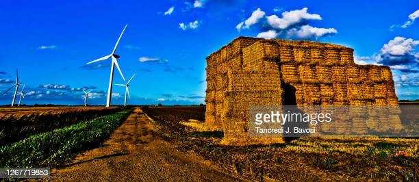 rural scene of haystack and wind turbine - bavosi stock pictures, royalty-free photos & images